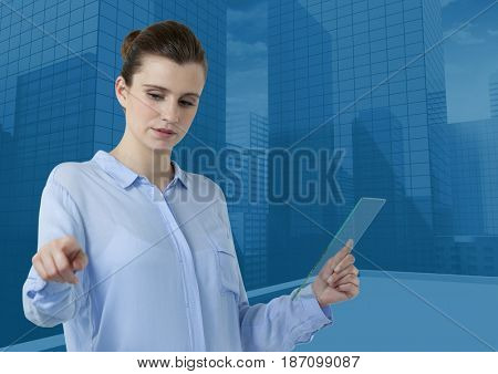 Digital composite of Woman touching air while holding glass tablet with blue city buildings background