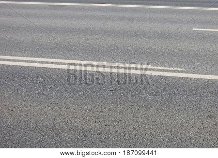 Gray asphalt highway with white stripes. Blank surface with place for text. Abstract background, urban wallpaper.