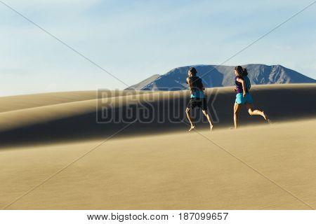 Hispanic couple running on sand dune