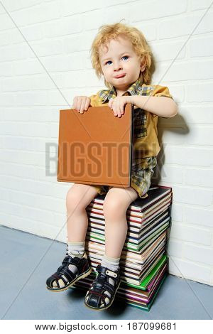 Cute little boy sitting on a stack of books with opened book. Educational concept.