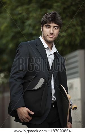 Caucasian businessman holding briefcase and skateboard