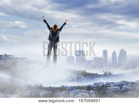 Digital composite of Business woman cheering on misty mountain peak against skyline