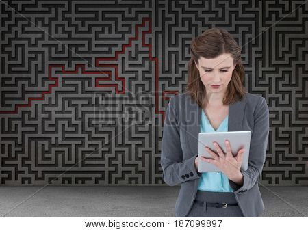 Digital composite of woman on tablet with maze background