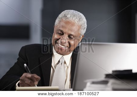 Black businessman writing on notepad at desk