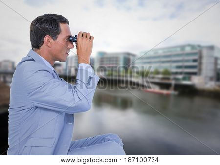 Digital composite of Business man with bionoculars against water across from blurry buildings
