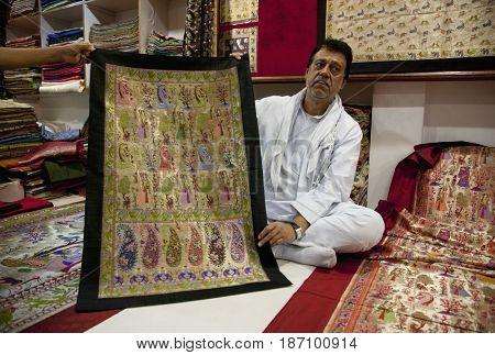 Indian man showing ornate carpet