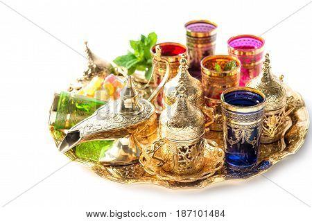 Golden tea service on white background. Colorful holidays decoration. Ramadan. Eid Mubarak