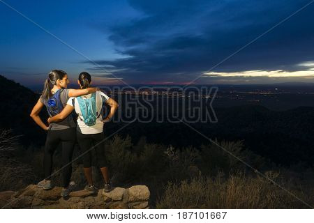 Hispanic women backpacking in remote area at night