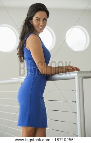 Hispanic woman leaning on railing