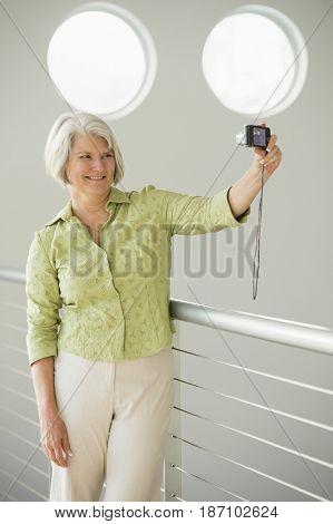 Caucasian woman taking digital self-portrait