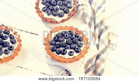 Blueberry Tarts On A White Wooden Board