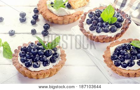 Sweet Blueberry Tarts On A White Wooden Background