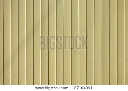 Light yellow goffered metal texture, corrugated steel surface. Industrial background.