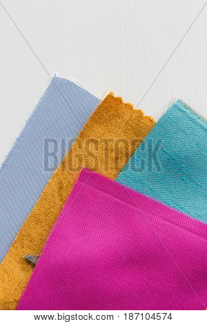 sewing, tailoring and fashion concept - beautiful colored patchwork fabric, flaps ready for stitching over white background, macro on tools at workshop, flat lay, top view, vertical