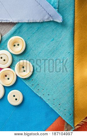 sewing, patchwork, tailoring and fashion concept - macro of desktop designer with white buttons and scraps of colored tissue, patches of blue, gray fabric, flat lay, top view, vertical