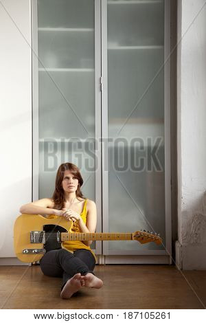 Woman sitting on floor with guitar