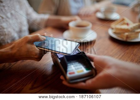 Human hand holding smartphone over payment terminal