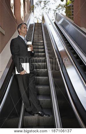 Hispanic businessman on escalator