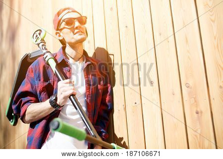 Rest of man with scooter standing at wooden fence. Free place