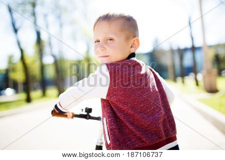 Boy riding bicycle along path in park