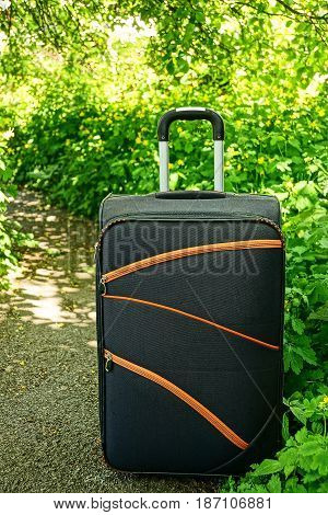 A large suitcase on wheels standing on a path near the green vegetation