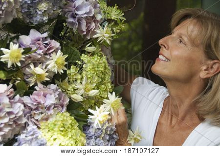 Caucasian woman looking at flowers