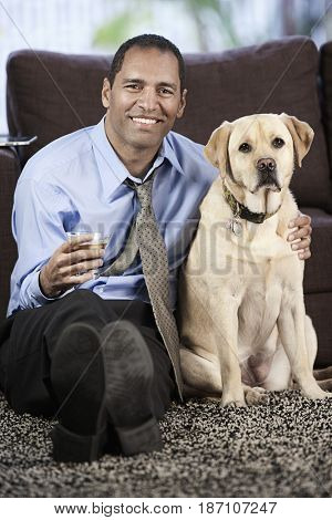Mixed race businessman drinking cocktail and petting dog