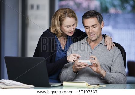 Caucasian couple using cell phone together