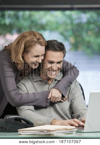 Caucasian couple hugging and looking at laptop