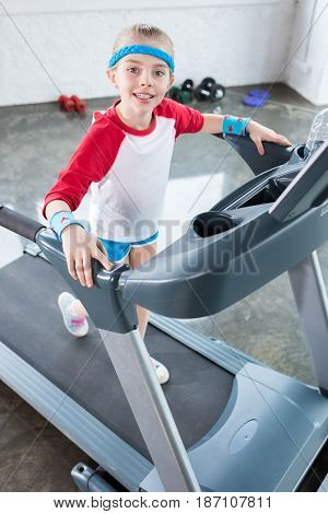 Adorable Kid Girl In Sportswear Training On Treadmill At Gym, Children Sport Concept