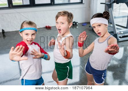 Group Of Little Kids In Sportswear Exercising And Posing At Camera In Gym, Children Sport School Con