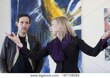 Caucasian woman talking to customer in art gallery