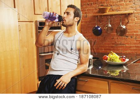 Hispanic man drinking water after exercise