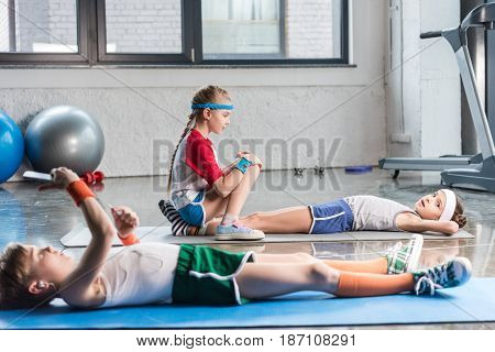 Little Boys Lying On Yoga Mat And Using Smartphone While Friends Exercising In Gym, Children Sport S