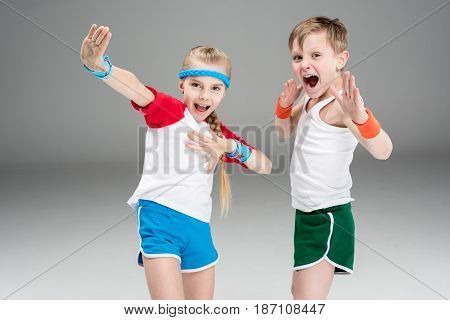 Sporty Boy And Girl In Sportswear Exercising And Gesturing Isolated On Grey, Children Sport Concept