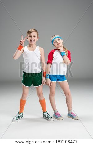Full Length View Of Cute Smiling Boy And Girl In Sportswear Standing Together And Gesturing Isolated