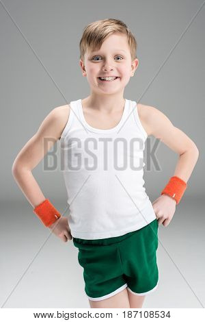 Adorable Little Boy In Sportswear Standing With Hands On Waist And Smiling At Camera, Children Sport