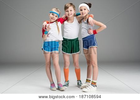 Adorable Smiling Sporty Kids In Sportswear Standing Together Isolated On Grey, Children Sport Concep