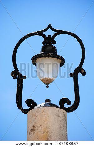 old iron street lamp on stone pilar