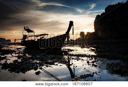 traditional long tail boat silhouette at low tide in sunset liights on Ton Sai beach, Thailand