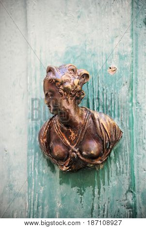 Old door handle on green painted wooden door