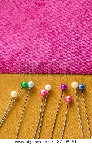 needlework, quilting, sewing and tailoring concept - beautiful cute purple and sand color patches with a lot of colorful pins, macro, flat lay, top view, vertical