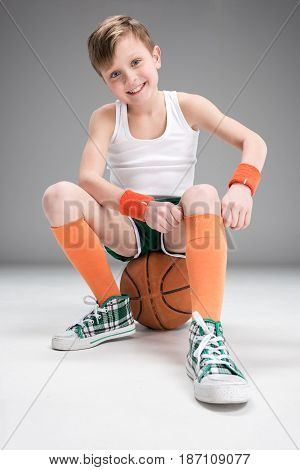 Smiling Boy In Sportswear Sitting On Basketball Ball Isolated On Grey