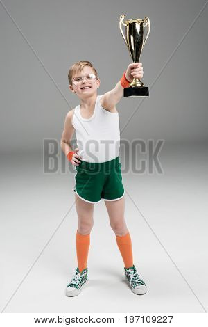 Smiling Boy Showing Champion's Goblet Isolated On Grey