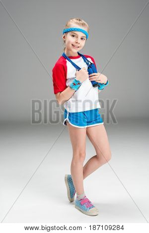 Smiling Girl In Sportswear Holding Skipping Rope Isolated On Grey