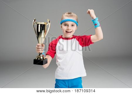 Portrait Of Excited Girl Holding Champion's Goblet Isolated On Grey