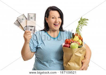 Joyful overweight woman with bundles of money and a bag filled with groceries isolated on white background