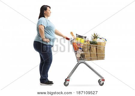 Full length profile shot of an overweight woman with a shopping cart full of groceries waiting in line isolated on white background