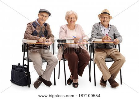 Seniors in school chairs taking notes and looking at the camera isolated on white background