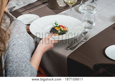 woman eating delicious salmon pasta in a restaurant. at the food and wine pairing. small portion.